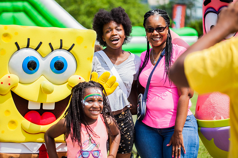 Kids and caregivers enjoying a family-friendly event with SpongeBob costume characters